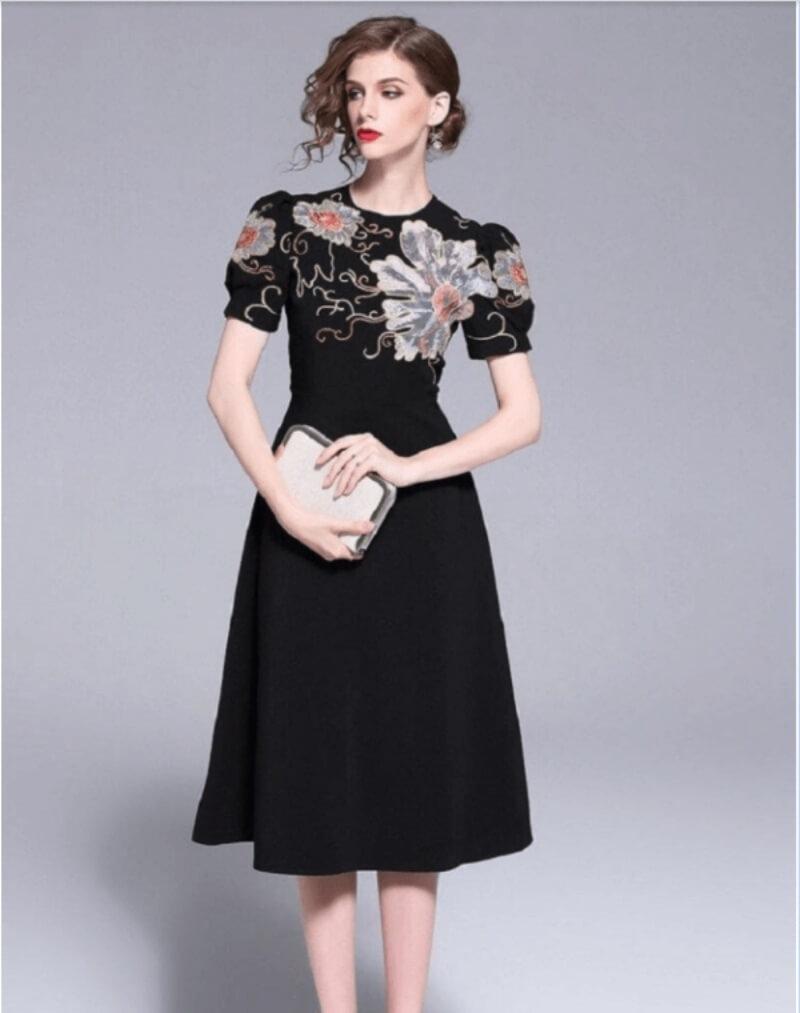 Đầm đen xòe họa tiết hoa lớn ở ngực mặc lên là chuẩn thần thái sang trọng